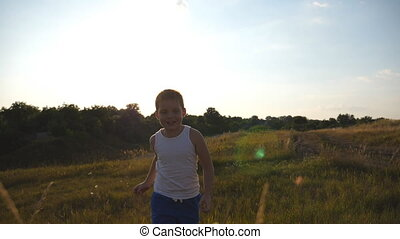 Portrait of happy little boy running at field behind camera. Smiling male kid having fun in nature on a summer meadow. Child jogging at the lawn outdoor on sunny day. Slow motion