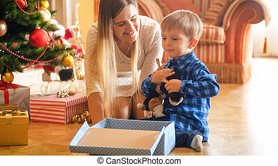 Portrait of happy little boy sitting under Christmas tree with open gift box
