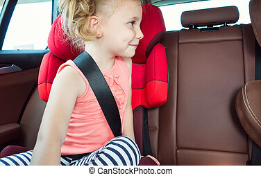 Portrait of happy little child girl sitting comfortable in car seat with safety belts enjoying ride in the auto