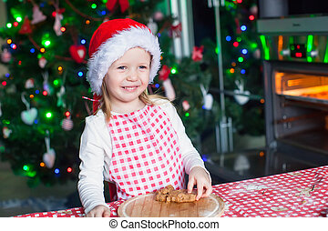 Portrait of happy little girl in the kitchen baking gingerbread