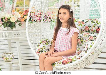 Portrait of happy little girl posing on swing