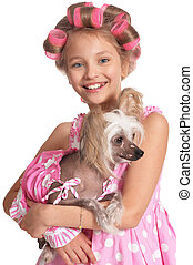 portrait of happy little pretty girl in hair curlers with dog in studio isolated on white background