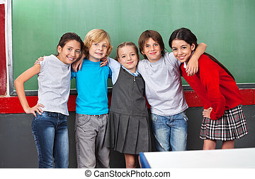 Portrait of happy little schoolchildren with arms around standing together against chalkboard in classroom