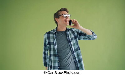 Portrait of happy male student talking on mobile phone gesturing and smiling