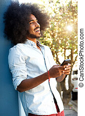 happy man leaning against wall with mobile phone