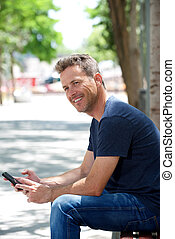 Portrait of happy man sitting on park bench with cellphone