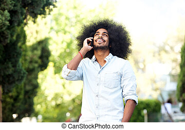 happy man standing outside in nature with mobile phone