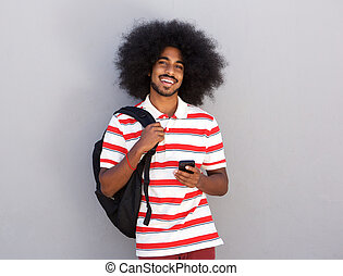 happy man with backpack and mobile phone
