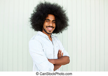 happy man with beard and afro standing with arms crossed