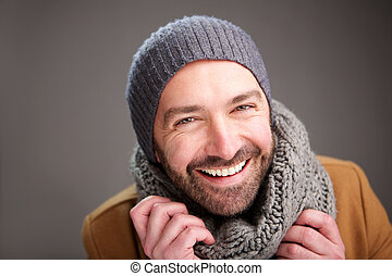 happy man with hat and scarf posing against gray wall
