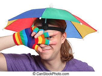 Portrait of happy man with rainbow hat umbrella on head and colorfull glove