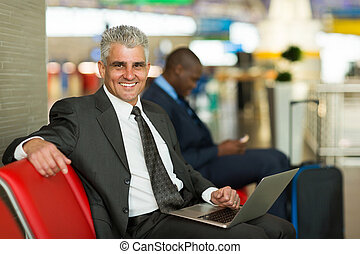 mature business traveler using laptop at airport