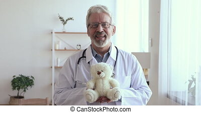 Portrait of happy middle aged elderly qualified kind children doctor in white coat holding toy. Smiling experienced friendly old mature male pediatrician with teddy bear in hands looking at camera.