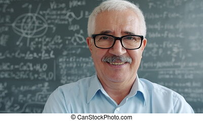 Portrait of happy mature man in glasses looking at camera smiling near chalkboard