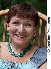 Portrait of happy mature woman in malachite bijou