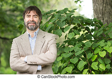 Portrait of happy middle-aged businessman looking at camera and smiling, outdoors
