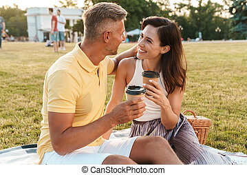 Portrait of happy middle-aged couple drinking coffee takeaway from paper cup while sitting on grass in park