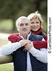 portrait of happy middle-aged couple posing in park