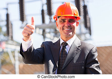 middle aged male industrial manager giving thumb up