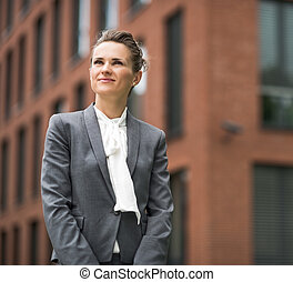 Portrait of happy modern business woman against office building