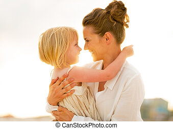 Portrait of happy mother and baby girl hugging on beach at the e