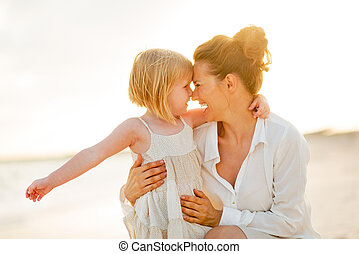 Portrait of happy mother and baby girl hugging on the beach in t
