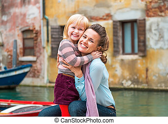 Portrait of happy mother and baby girl hugging while in venice,