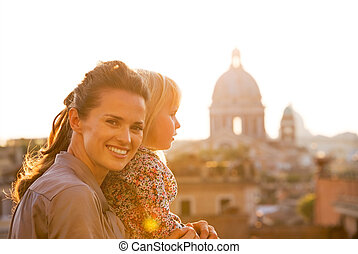 Portrait of happy mother and baby girl on street overlooking...