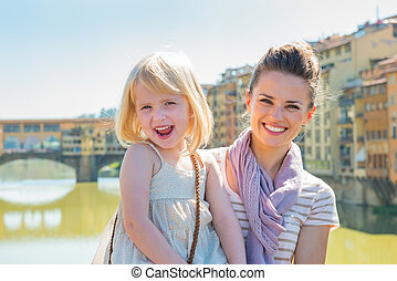 Portrait of happy mother and baby girl standing on bridge...