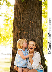 Portrait of happy mother and baby girl having fun in park