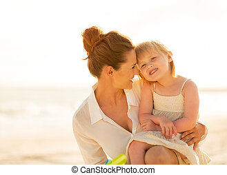 Portrait of happy mother and baby girl on the beach in the...