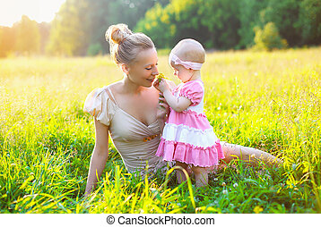 Portrait of happy mother and baby little daughter wearing a dress in sunny summer day together on the grass meadow