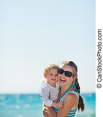 Portrait of happy mother and baby on beach