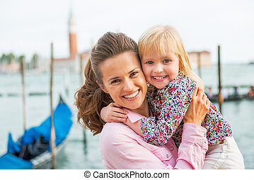 Portrait of happy mother and baby on grand canal embankment ...