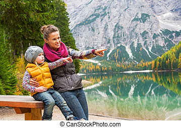 Portrait of happy mother and baby on lake braies in south tyrol,