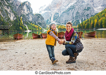 Portrait of happy mother and baby on lake braies in south ...