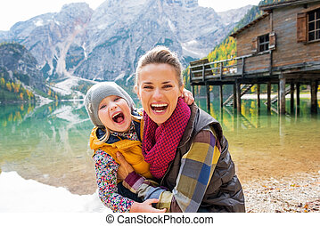 Portrait of happy mother and baby on lake braies in south...
