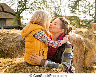 Portrait of happy mother and child kissing while sitting on hays