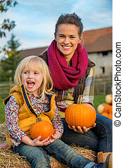 Portrait of happy mother and child sitting on haystack and holdi