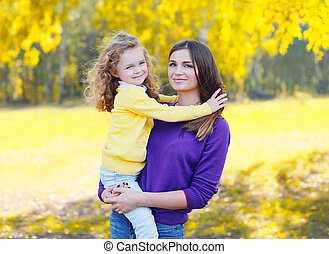 Portrait of happy mother and child together in autumn park