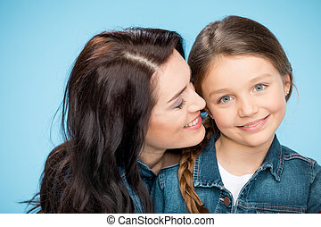 portrait of happy mother and daughter hugging in studio on blue