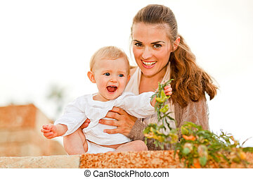 Portrait of happy mother and laughing baby playing with plants