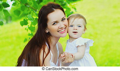 Portrait of happy mother and little girl baby on the grass in a summer park