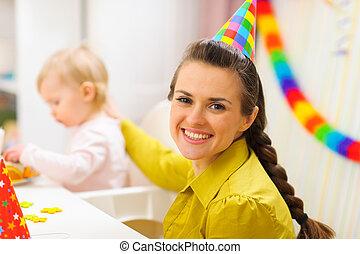Portrait of happy mother celebrating baby first birthday