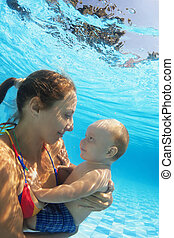 Portrait of happy mother with child swimming underwater in pool