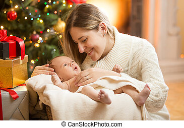 happy mother with newborn baby under Christmas tree
