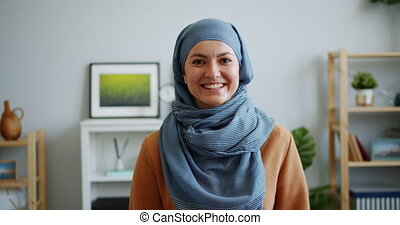 Portrait of happy Muslim lady in hijab smiling looking at...