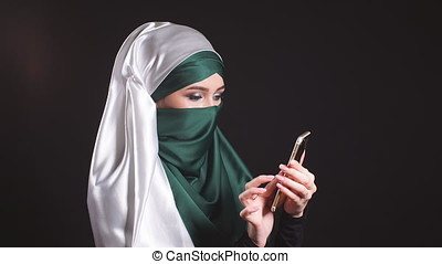 Portrait of happy muslim woman using mobile phone. -...