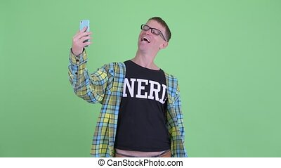 Portrait of happy nerd man taking selfie - Studio shot of...