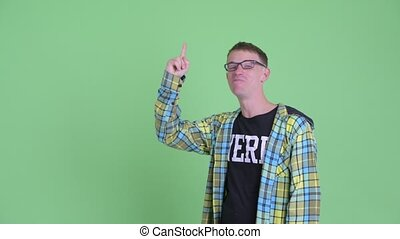 Portrait of happy nerd man talking while pointing up -...